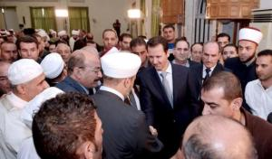 Syria's President Bashar al-Assad greets a cleric after attending prayers on the first day of Eid al-Adha at al-Adel mosque in Damascus, Syria, in this handout photograph released by Syria's national news agency SANA on September 24, 2015. REUTERS/SANA/Handout via Reuters