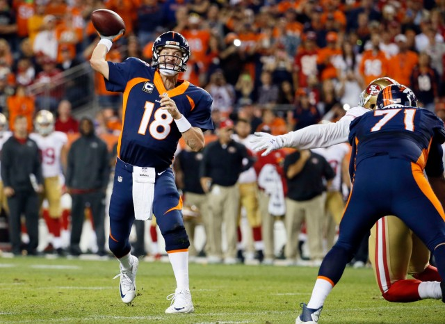 FILE - In this Oct. 19, 2014, file photo, Denver Broncos quarterback Peyton Manning throws his 509th career touchdown pass to set the all time record during the first half of an NFL football game against the San Francisco 49ers, in Denver. Manning's receivers played keep-away with his milestone memento after he broke Brett Favre's all-time record with his 509th TD throw, an 8-yard strike to receiver Demaryius Thomas. (AP Photo/Jack Dempsey, File)