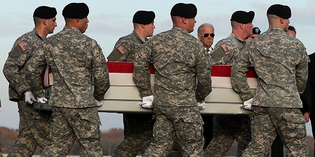 WASHINGTON, DC - NOVEMBER 15: Members of a U.S. Army carry team move the flag-draped transfer case holding the remains of Army Pfc. Tyler R. Iubelt of Tamaroa, Illinois, as they pass by Vice President Joseph Biden during a dignified transfer at Dover Air Force Base November 15, 2016 in Dover, Delaware. Iubelt, 20, who was assigned to Headquarters and Headquarters Company, 1st Special Troops Battalion, 1st Sustainment Brigade, 1st Cavalry Division in Fort Hood, Texas, died November 12 of injuries sustained from a suicide bomb attack at Bagram Airfield near Kabul in Afghanistan. (Photo by Alex Wong/Getty Images)