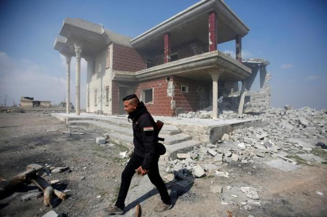 A Sunni Arab fighter walks near a house, which the residents of the village said belonged to a man who joined the Islamic State militants and was destroyed in an explosion, in Rfaila village in the south of Mosul, Iraq, February 17, 2017. REUTERS/Khalid al Mousily