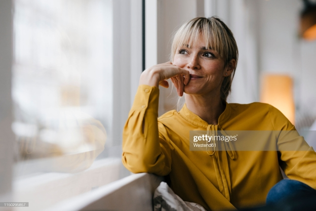 This image has an empty alt attribute; its file name is portrait-of-a-beautiful-blond-woman-looking-out-of-window-picture-id1150295857.jpg